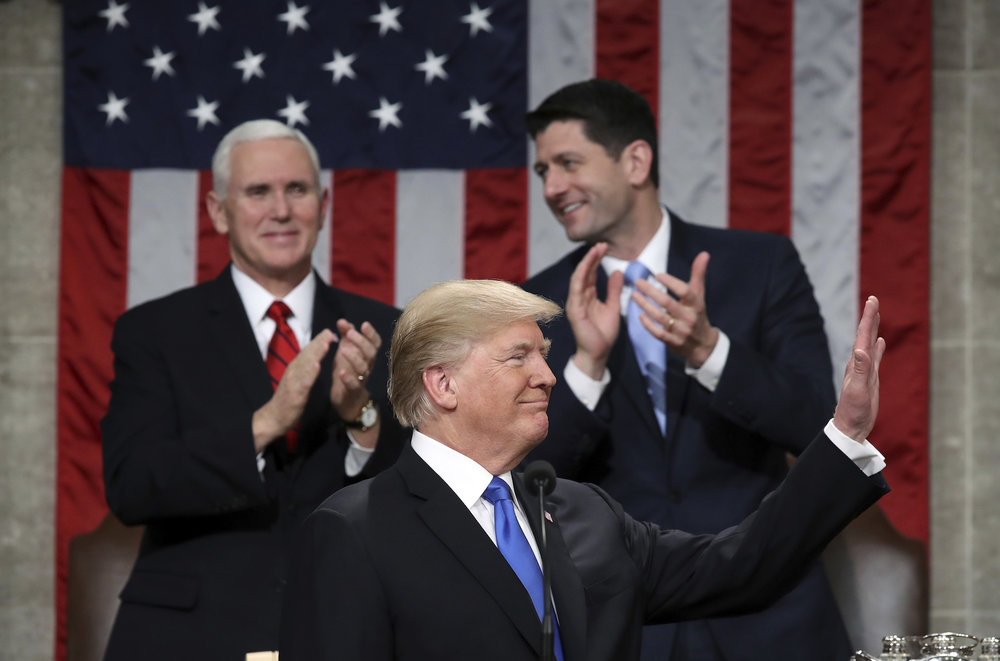 President Donald Trump waves during his first State of the Union address in the House chamber of the U.S. Capitol to a joint session of Congress Tuesday, Jan. 30, 2018 in Washington, as Vice President Mike Pence and House Speaker Paul Ryan applaud. (Win McNamee/Pool via AP)