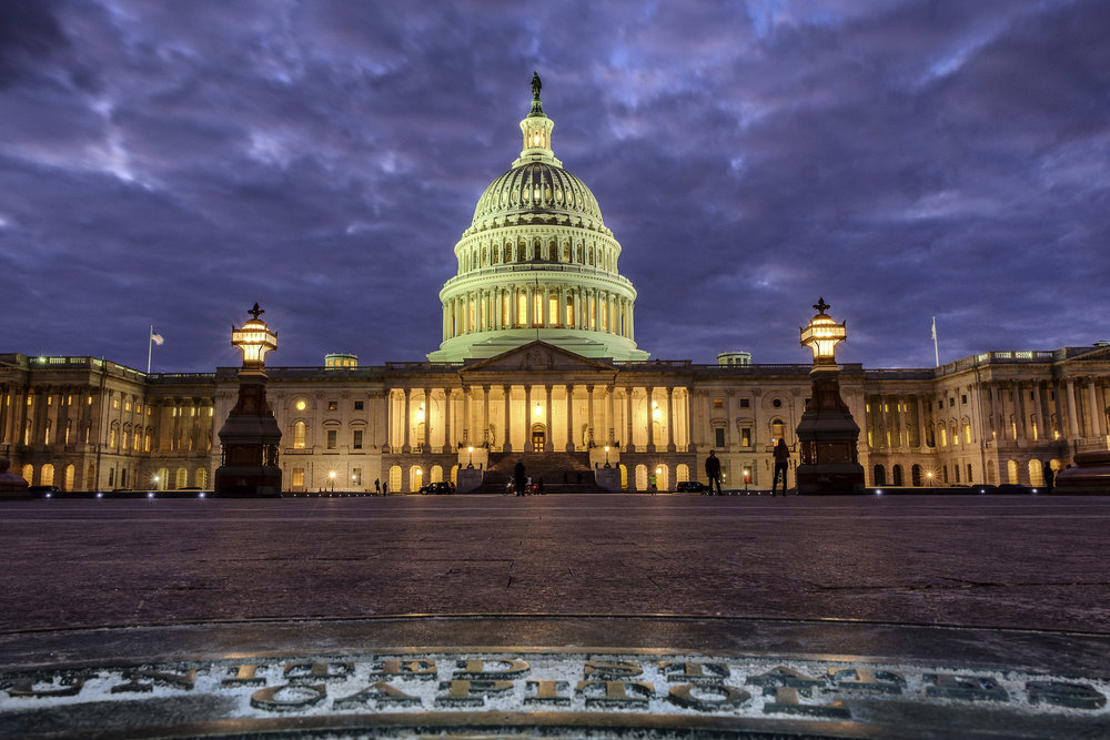 In this Jan. 21, 2018, photo, lights shine inside the U.S. Capitol Building as night falls in Washington. (AP Photo/J. David Ake)