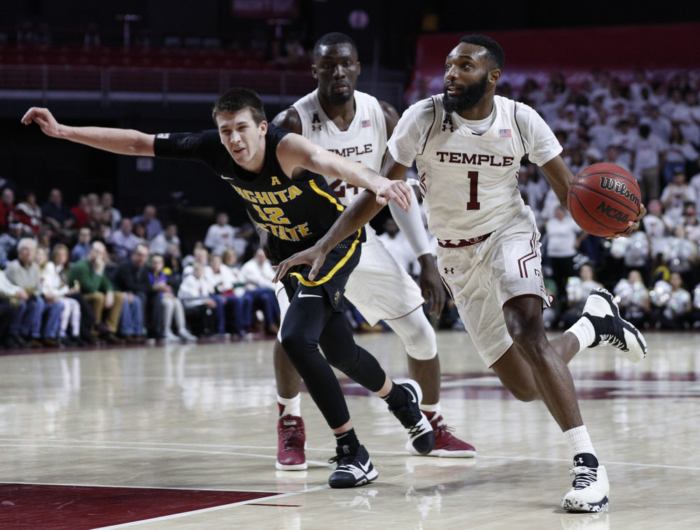 Temple's Josh Brown, right, drives to the basket against Wichita State's Austin Reaves, left, during the second half of an NCAA basketball game, Thursday, Feb. 1, 2018, in Philadelphia. Temple won 81-79 in overtime. (AP Photo/Chris Szagola)