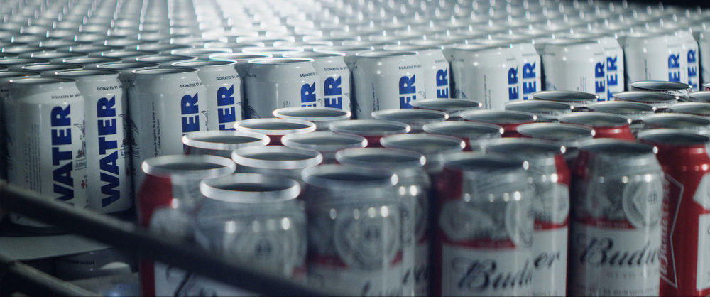 This photo provided by Budweiser shows a scene from the company's Super Bowl spot. It was the most effective commercial in which one of the company's factories repurposed their cans, filled them with water and sent them to those in need of disaster relief. (Budweiser via AP)