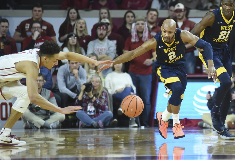 West Virginia's Jevon Carter (2) tries to get to the ball before Oklahoma's Jamuni McNeace (4) in the first half of an NCAA college basketball game in Norman, Okla., Monday, Feb. 5, 2018. (Kyle Phillips/AP)
