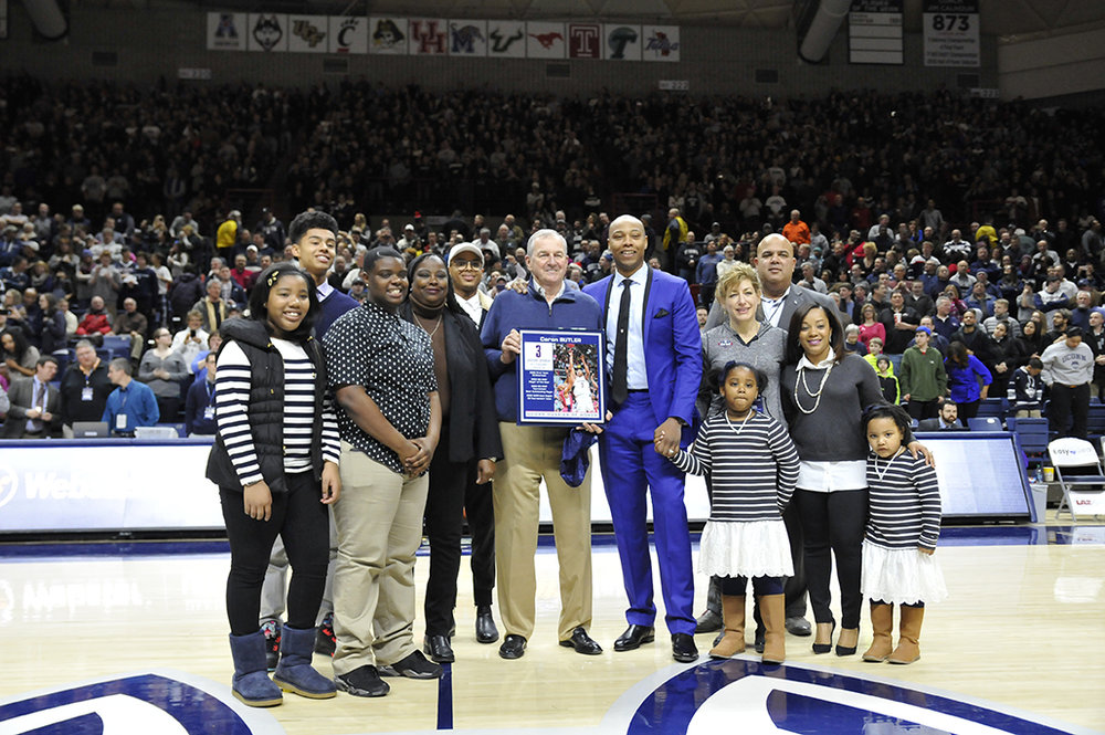 Caron Butler (seventh from the left) accepts a plaque as he enters the Huskies of Honor on Feb. 3, 2016. He is joined on the court at Gampel Pavilion by his family, former coach Jim Calhoun, UConn President Susan Herbst, and former athletic director Warde Manuel. (Jason Jiang/The Daily Campus)