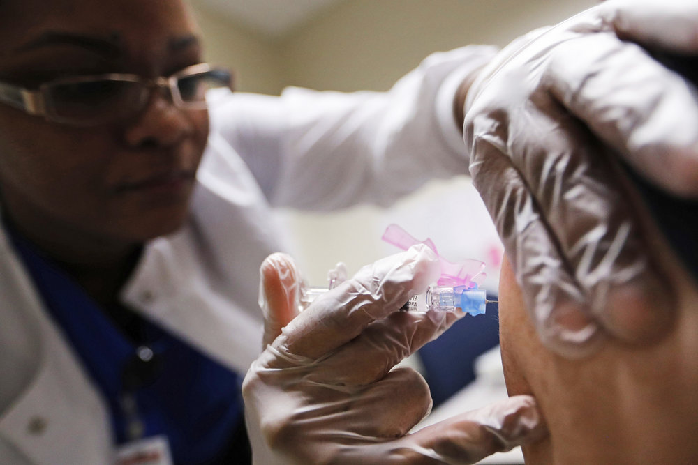 Registered Nurse Claudina Prince administers a flu shot at a Dekalb County health center in Decatur, Ga., Monday, Feb. 5, 2018. The U.S. government's latest flu report released on Friday, Feb. 2, 2018, showed flu season continued to intensify the previous week, with high volumes of flu-related patient traffic in 42 states, up from 39 the week before. (David Goldman/AP)