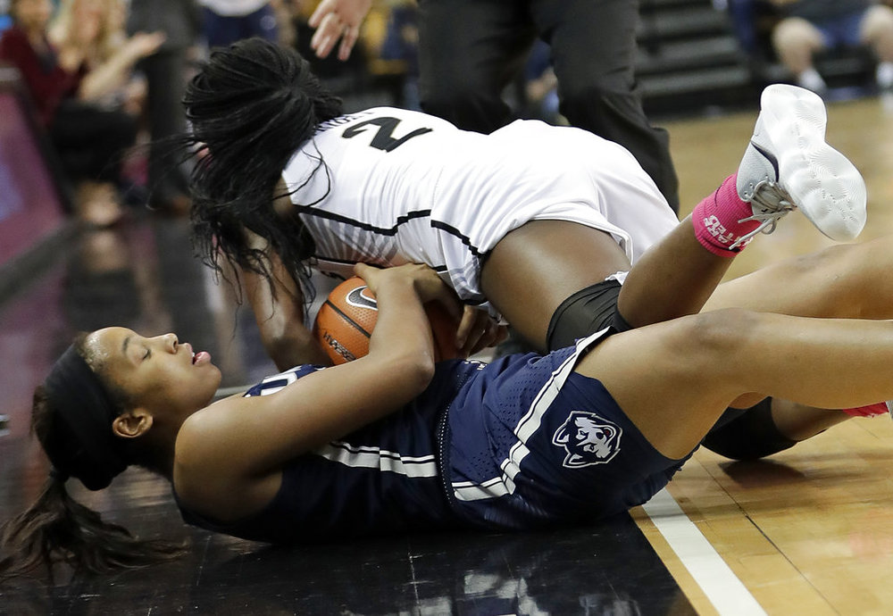 Connecticut's Megan Walker, left, and Central Florida's Korneila Wright (2) battle for a loose ball during the second half of an NCAA college basketball game, Wednesday, Feb. 7, 2018, in Orlando, Fla. Connecticut won 55-37. (AP Photo/John Raoux)