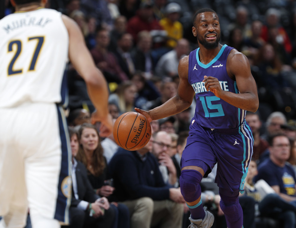 Charlotte Hornets guard Kemba Walker, back, drives down the court with the ball as Denver Nuggets guard Jamal Murray backs up on defense in the first half of an NBA basketball game Monday, Feb. 5, 2018, in Denver. (AP Photo/David Zalubowski)