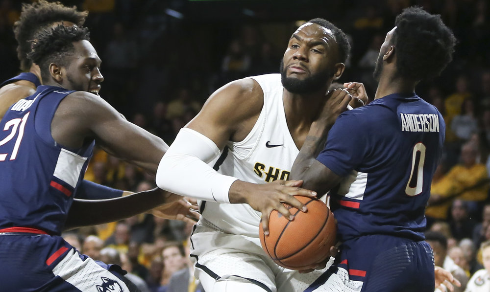 Wichita State center Shaquille Morris, center, is fouled by Connecticut guard Antwoine Anderson during the second half of an NCAA college basketball game Saturday, Feb. 10, 2018, in Wichita, Kan. (Travis Heying/The Wichita Eagle via AP)