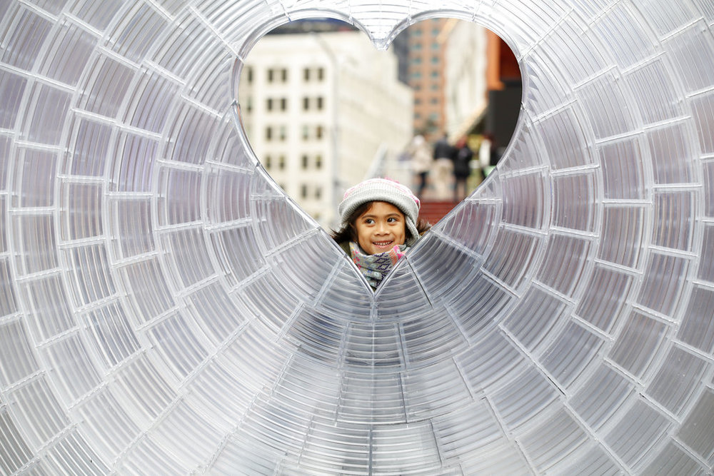"Moni Jaimes, of Queretaro, Mexico, peers through a heart-shaped window as a family member takes her photo, at ""Window to the Heart,"" a Valentine's Day themed art installation in Times Square, Thursday, Feb. 1, 2018, in New York. (AP Photo/Kathy Willens)"