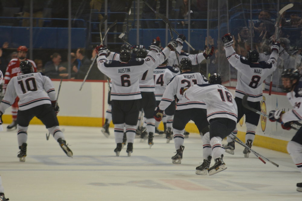 The Huskies celebrate after Friday nights victory (Jon Sammis/The Daily Campus)