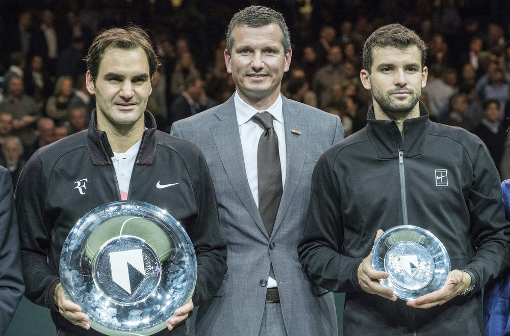 Roger Federer, left, of Switzerland holds the trophy as he celebrates winning his match against Bulgaria's Grigor Dimitrov, right, in two sets, 6-2, 6-2, in the men's singles final of the ABN AMRO world tennis tournament at the Ahoy stadium in Rotterdam, Netherlands, Sunday, Feb. 18, 2018. At center is tournament director Richard Krajicek. (AP Photo/Patrick Post)