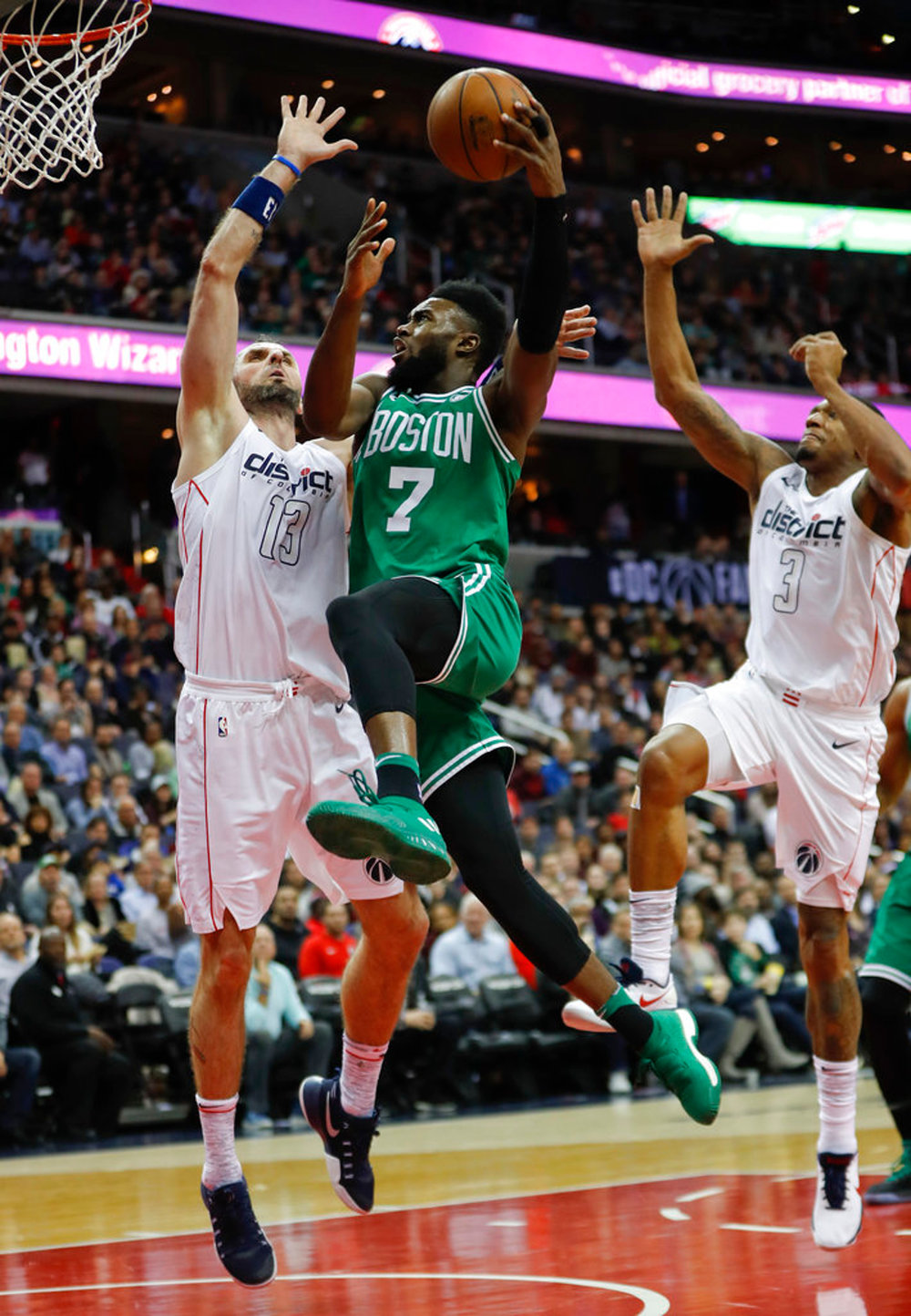 Boston Celtics guard Jaylen Brown (7) drives past Washington Wizards center Marcin Gortat (13), from Poland, and Bradley Beal (3) during the second half of an NBA basketball game Thursday, Feb. 8, 2018, in Washington. (AP Photo/Pablo Martinez Monsivais)