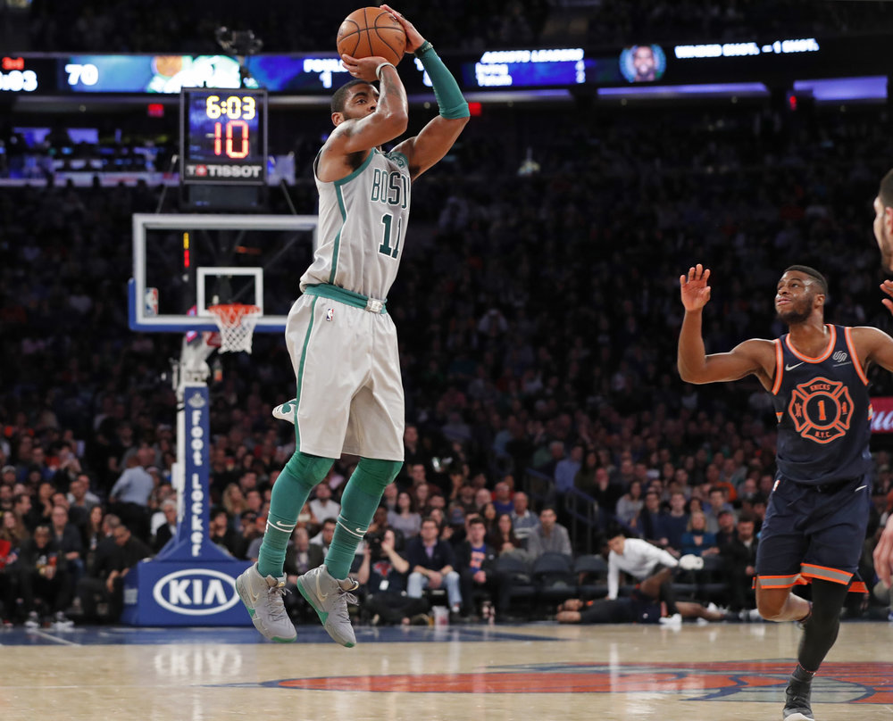 Boston Celtics guard Kyrie Irving (11) shoots as New York Knicks guard Emmanuel Mudiay (1) watches from the floor during the second half of an NBA basketball game in New York, Saturday, Feb. 24, 2018. (AP Photo/Kathy Willens)