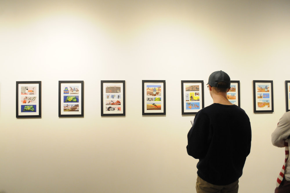 "Students admire Austin MacDonald's cut-paper comic ""Prodigal- The Sentinel's Garden"" Tuesday night, Feb. 27 in the Art Building Room 109. (Natalija Marosz/The Daily Campus)"