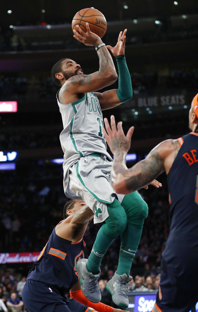 Boston Celtics guard Kyrie Irving, center, shoots over New York Knicks guard Trey Burke, during an NBA basketball game in New York, Saturday, Feb. 24, 2018. (AP Photo/Kathy Willens)