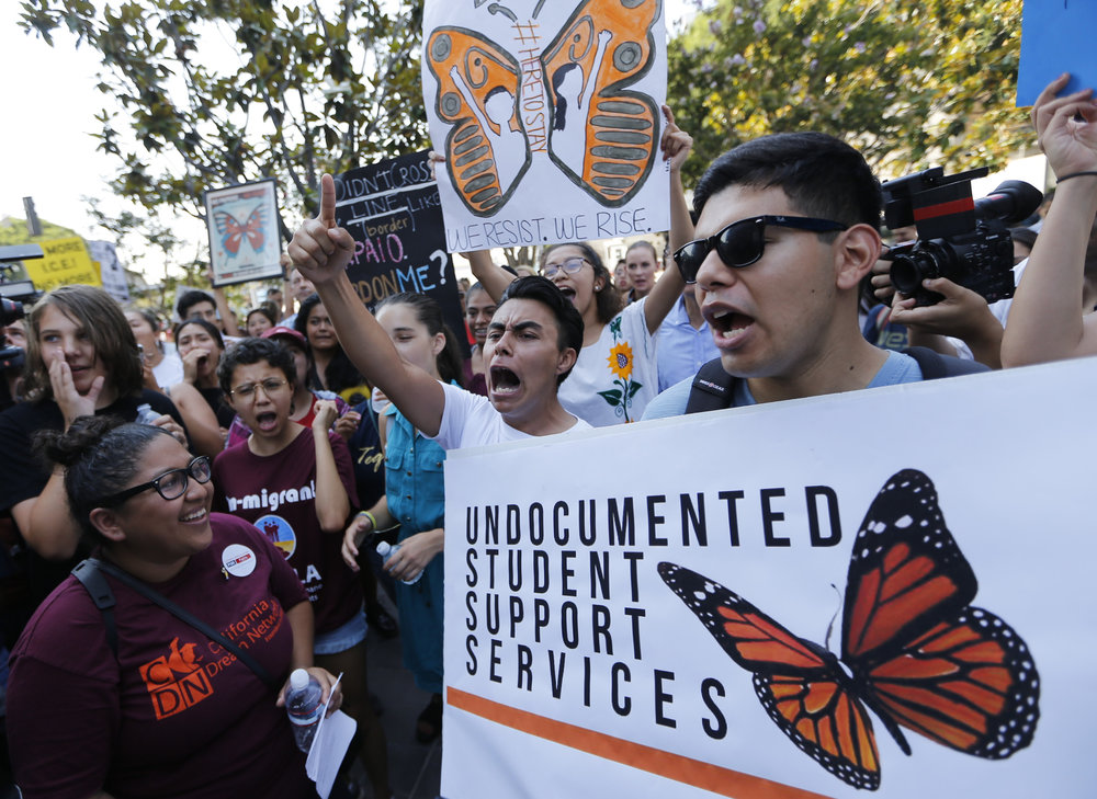 FILE - In this Sept. 1, 2017, file photo, Undocumented students join a rally in support of the Deferred Action for Childhood Arrivals, or DACA program, outside the Edward Roybal Federal Building in downtown Los Angeles. A program that temporarily shields hundreds of thousands of young people from deportation was scheduled to end Monday, March 5, 2018, but court orders have forced the Trump administration to keep issuing renewals, easing the sense of urgency. (AP Photo/Damian Dovarganes, File)