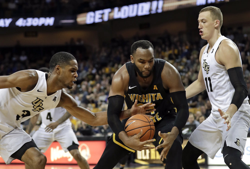 Central Florida's A.J. Davis, left, tries to steal the ball from Wichita State's Shaquille Morris, center, as Rokas Ulvydas, right, comes in to help during the second half of an NCAA college basketball game, Thursday, March 1, 2018, in Orlando, Fla. (AP Photo/John Raoux)
