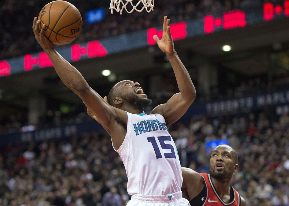Charlotte Hornets guard Kemba Walker (15) is fouled by Toronto Raptors' Serge Ibaka during the fourth quarter of an NBA basketball game, Sunday, March 4, 2018, in Toronto. The Raptors beat the Hornets 103-98. (Frank Gunn/The Canadian Press via AP)