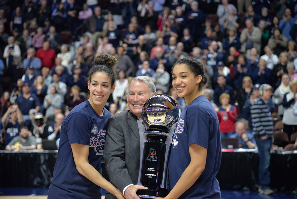 Seniors Kia Nure and Gabby Williams are handed the AAC Championship trophy by conference Commission Mike Aresco after defeating USF on Tuesday, March 6, 2018. (Amar Batra/The Daily Campus)