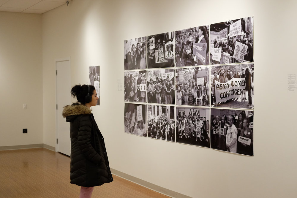 """LJ Karam looks at composite photograph in UConn Idea Grant and Greene Travel Award recipient Kiana Cao's exhibit titled """"An Examination of Immigration: A look into Buddhism, Community and Refugees"""" in the Jorgensen Art Gallery on Thursday, March 5, 2018. (Jon Sammis/The Daily Campus)"""