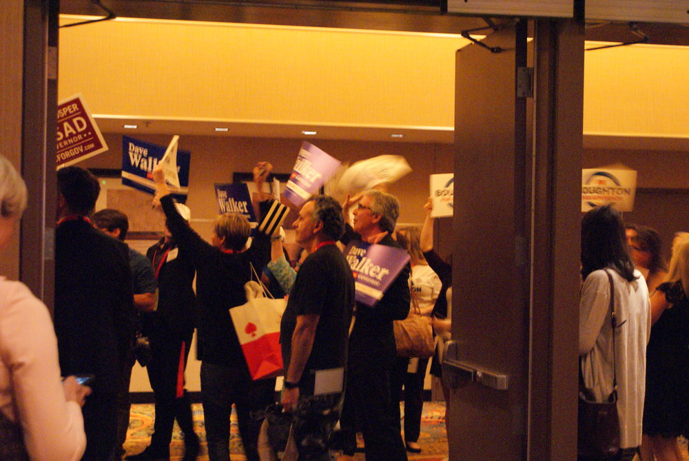 Supporters for all different candidates for governor stand outside the ballroom hoping to catch a glimpse of their candidate as they enter the convention floor.
