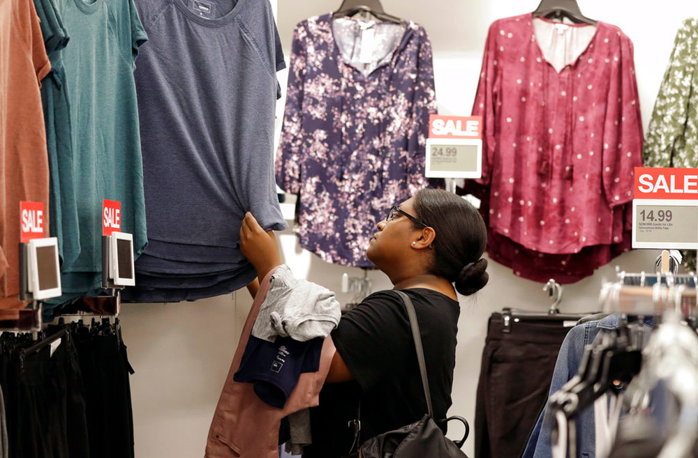 In this Tuesday, Aug. 28, 2018, photo, Heather Camacuari, of Charlotte, shops for clothing at a Kohl's store in Concord, N.C. Many kinds of chains have posted strong sales, both online and at stores. A booming economy, which has shoppers spending more freely, and companies' own efforts in trying to Amazon-proof their business is driving people's mood to spend. (AP Photo/Chuck Burton)