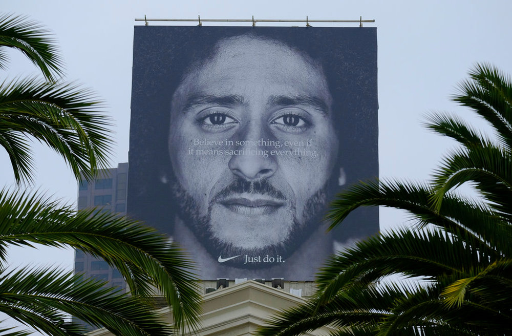 Palm trees frame a large billboard on top of a Nike store that shows former San Francisco 49ers quarterback Colin Kaepernick at Union Square, Wednesday, Sept. 5, 2018, in San Francisco. An endorsement deal between Nike and Colin Kaepernick prompted a flood of debate Tuesday as sports fans reacted to the apparel giant backing an athlete known mainly for starting a wave of protests among NFL players of police brutality, racial inequality and other social issues. (AP Photo/Eric Risberg)