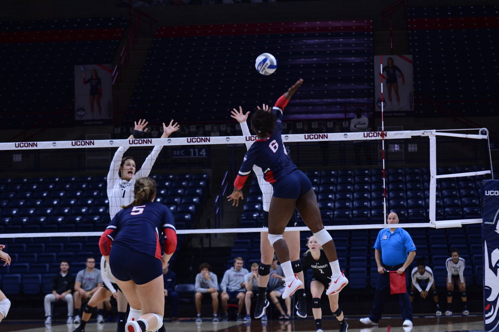 Kennadie Jake-Turker spikes the ball against a Cincinnati block during a game on Sunday, Oct. 7 at Gampel Pavilion. (Judah Shingleton, Staff Photographer/The Daily Campus)