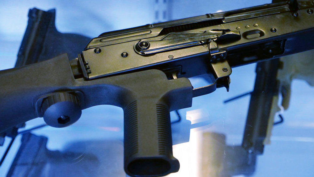 "FILE - This Oct. 4, 2017 file photo shows a device called a ""bump stock"" attached to a semi-automatic rifle at a gun store and shooting range in Utah. What's happened to bump stocks in the year since Las Vegas? There were growing calls to ban the devices in the immediate aftermath of the mass shooting on the Las Vegas strip. Some succeeded, but others did not. (AP Photo/Rick Bowmer, File)"