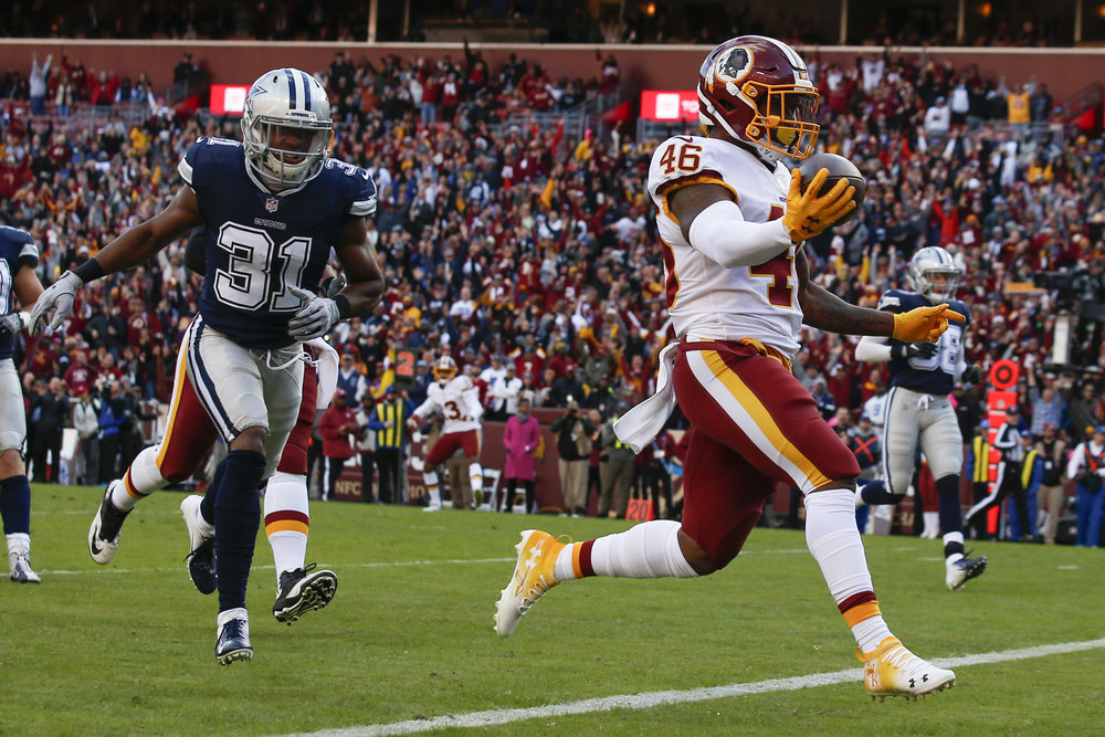 Kapri Bibbs carries the ball into the end zone for a touchdown as Byron Jones (31) chases him. Sunday, Oct. 21, 2018 in Landover, Md. (AP Photo/Alex Brandon)