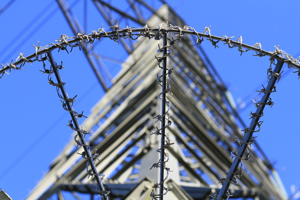 Barbed wire surrounds a tower at a prison. (Photo courtesy of Flickr Creative Commons)