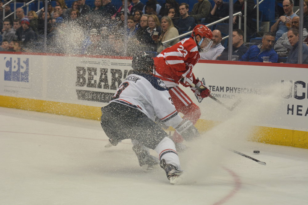 UConn sophomore Adam Karashik plays the puck in the boards during a game against Boston University. (File Photo/ The Daily Campus)