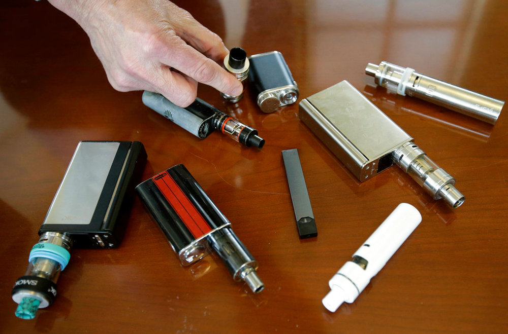 FILE - In this Tuesday, April 10, 2018, file photo, a high school principal displays vaping devices that were confiscated from students in such places as restrooms or hallways at the school in Massachusetts. The Food and Drug Administration is planning on requiring strict limits on the sale of most flavored e-cigarettes, including age verification controls for online sales, in an effort to curtail their use among children and teenagers. FDA officials tell The Wall Street Journal on Thursday, Nov. 8, the actions are expected to be announced as early as the following week. (AP Photo/Steven Senne, File)