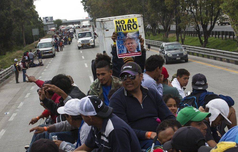 """A Central American migrant holds a sign with a message that reads in Spanish: """"No to the wall Trump"""", while hitching a ride on a truck in Tepotzotlan, Mexico, Saturday, Nov. 10, 2018. Thousands of Central American migrants were back on the move toward the U.S. border Saturday, after dedicated Mexico City metro trains whisked them to the outskirts of the capital and drivers began offering rides north. (AP Photo/Rodrigo Abd)"""