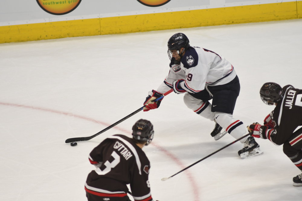UConn Men's Hockey carries the puck into the offensive zone against Brown on Nov. 13, 2018. (Eric Wang/ The Daily Campus)