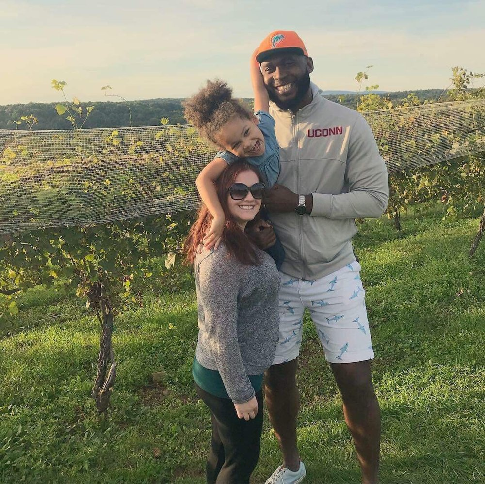 Former UConn men's basketball player Charles Okwandu smiles with his wife Kelsey and daughter Summer. (Photo courtesy of Charles Okwandu)