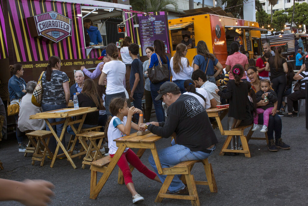 People eat at a food truck fair in Altamira neighborhood of Caracas, Venezuela, Sunday, Feb. 10, 2019. Last year, inflation in the South American country hit 1 million percent. (AP Photo/Rodrigo Abd)