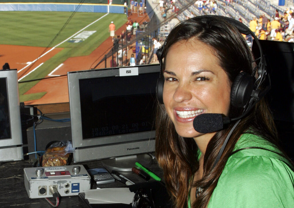 """FILE - In this May 29, 2009, file photo, USA softball player Jessica Mendoza poses for a photo in the ESPN broadcast booth at the Women's College World Series in Oklahoma City. Mendoza has been hired as a baseball operations adviser for the New York Mets while remaining a broadcaster for ESPN's """"Sunday Night Baseball."""" The move, announced Tuesday, March 5, 2019, is part of an increasing number of television commentators who also work for teams. (AP Photo/File)"""