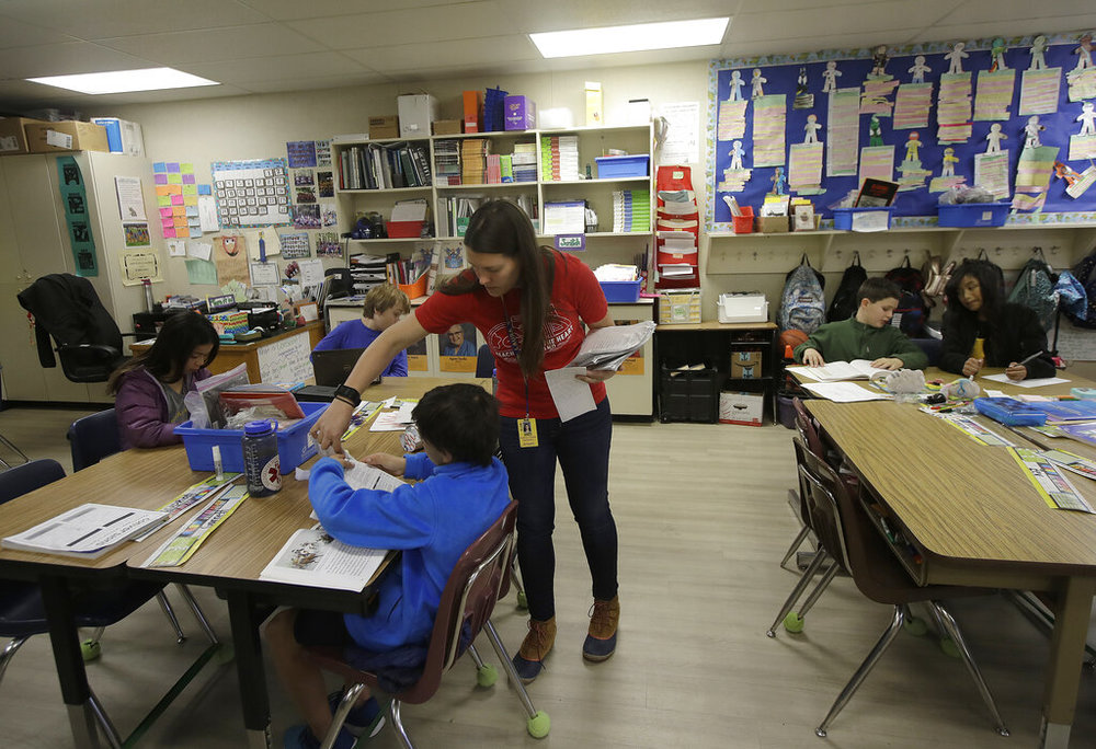Chabot Elementary School fourth grade teacher Laura Shield talks with a student in her class in Oakland, Calif., Monday, March 4, 2019. Thousands of Oakland teachers are back in classrooms after union members voted to approve a contract deal. (AP Photo/Jeff Chiu)