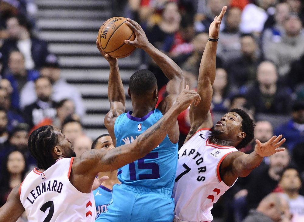 Charlotte Hornets guard Kemba Walker (15) drives between Toronto Raptors forward Kawhi Leonard, left, and guard Kyle Lowry during the first half of an NBA basketball game Sunday, March 24, 2019, in Toronto. (Frank Gunn/The Canadian Press via AP)