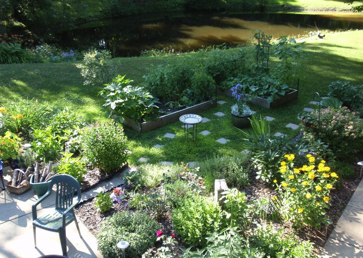 A beautiful edible landscape featuring a mixture of veggies, herbs, berries, and perennial flowers.