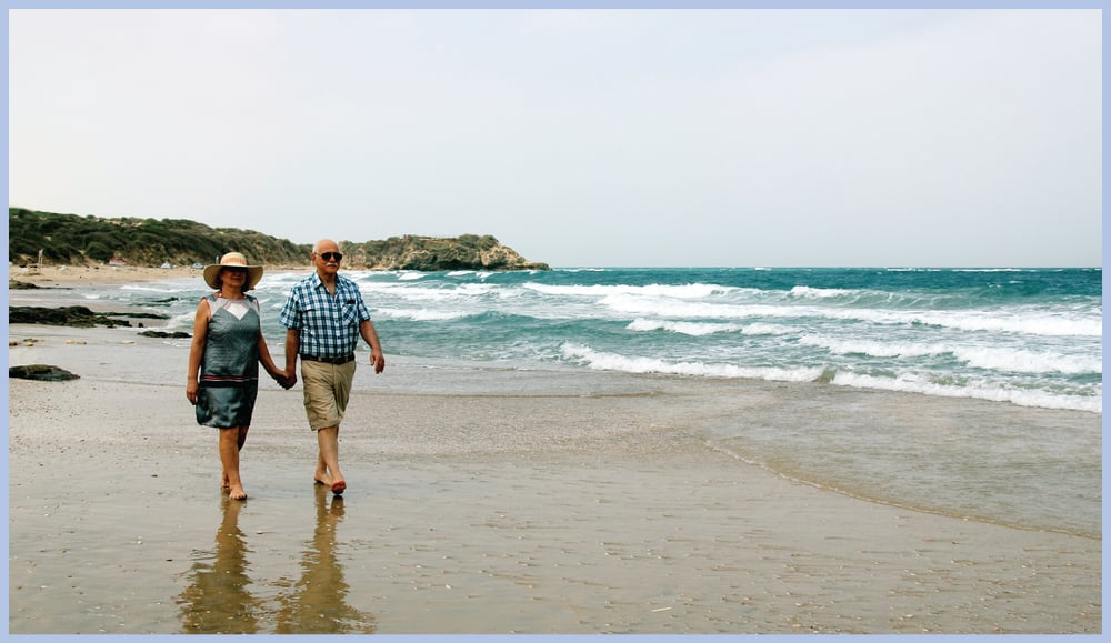 Man and woman walking on beach.
