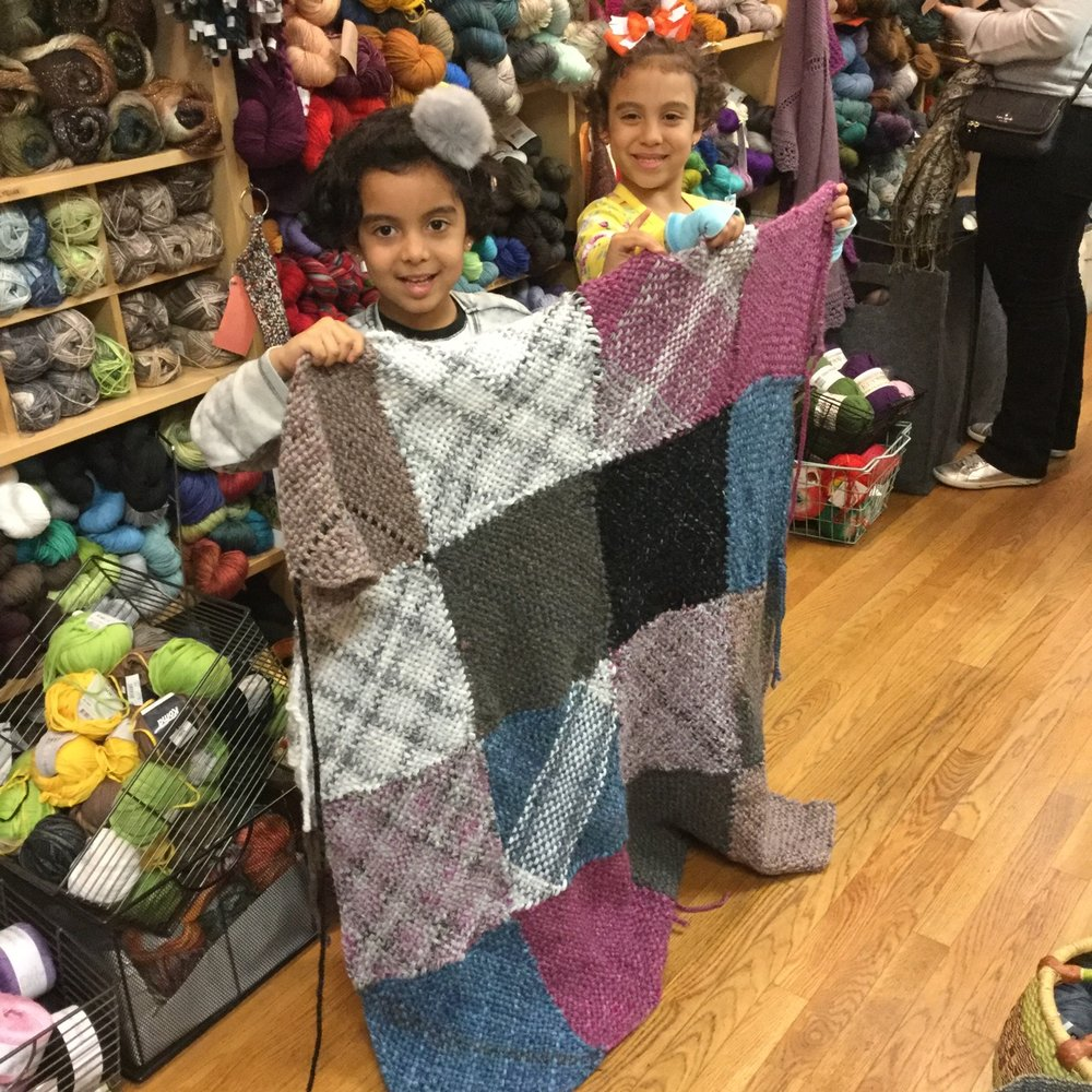Oriana and Rafaela proudly present their woven Welcome Blanket.