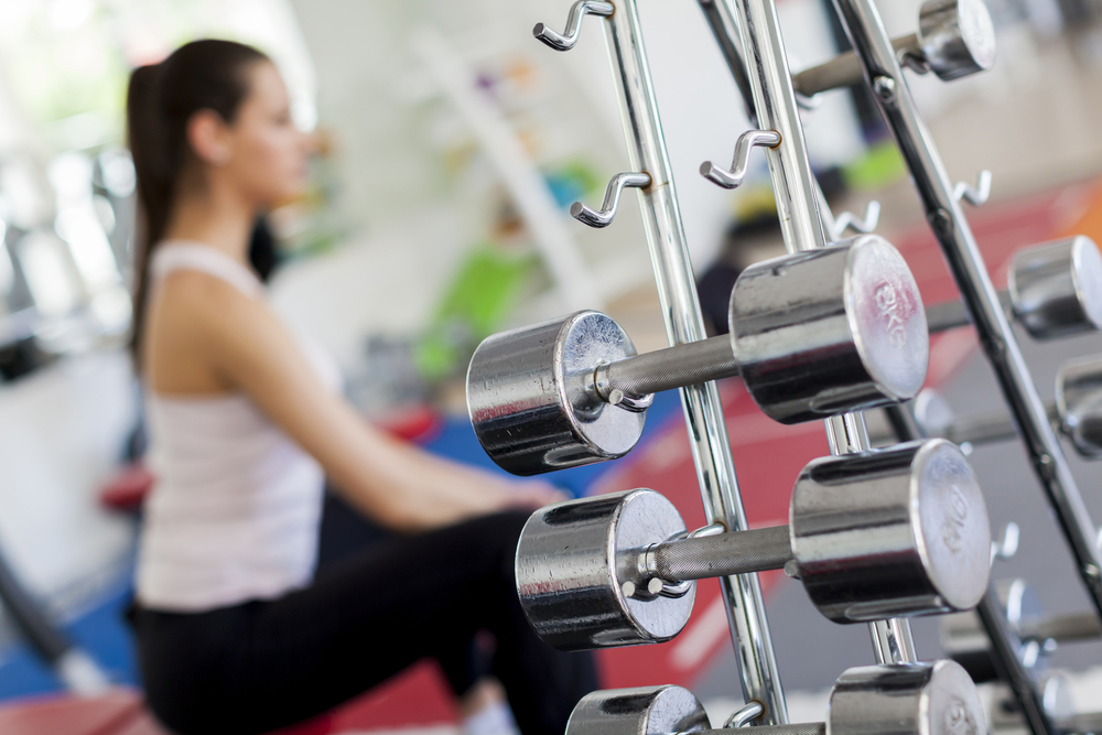 Girl In Fitness Room Gym Exercising Equipment.jpg