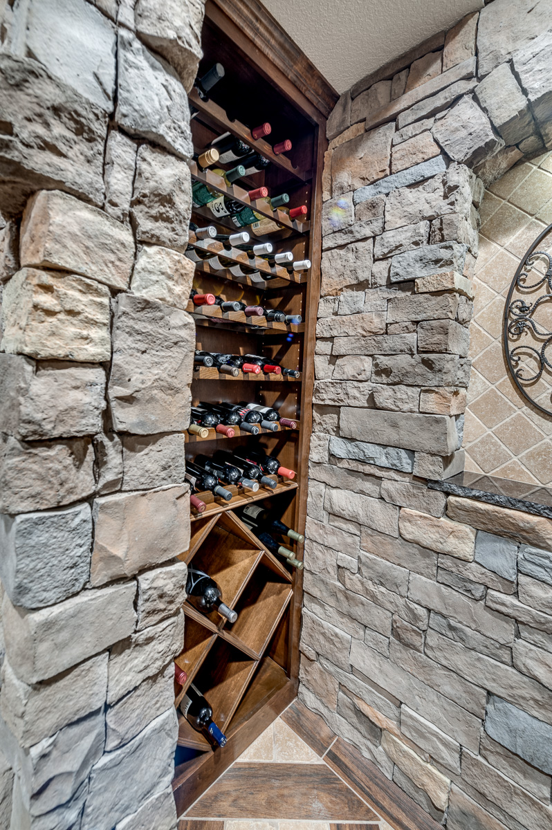 The wine cellar is equipped to have the owners and guests peruse a vast collection of wines. The wood used picks up the same wood tones in the flooring.