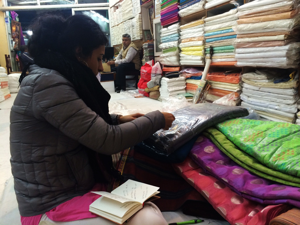 Textile shopping is a process that is very service oriented where the salesperson assists in picking out the best pieces that the shop has to offer. Here we see Reshma quality checking her favorite picks after the salesman unfurled them for her.