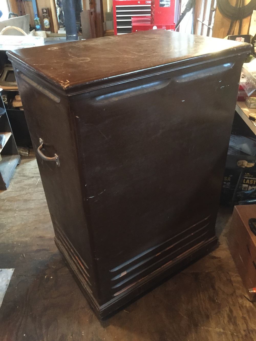 Cabinet needs repair. Painted brown, with handles and wobbly casters