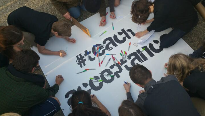 Students signing the #teachacceptance banner at the March 12 Speak Out rally. (Photo by @2hip4tv )