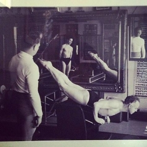 Joe Pilates teaching swan dive on the Wunda Chair in his original studio in NYC.
