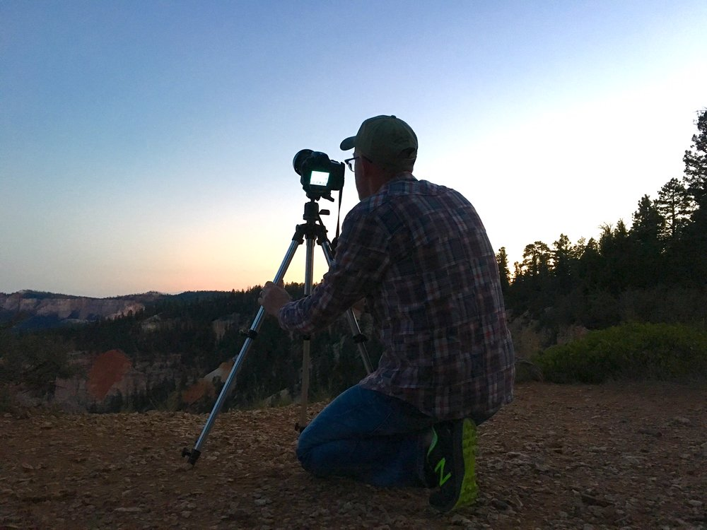 Dad sets up his gear on the edge of a cliff in Bryce Canyon National Park waiting for the sun to go down.  iPhone 6s.