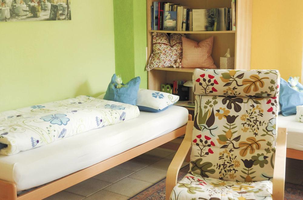 Studio: Ansicht des Betts, Stuhl im Vordergrund, Büchergestell im Hintergrund.
