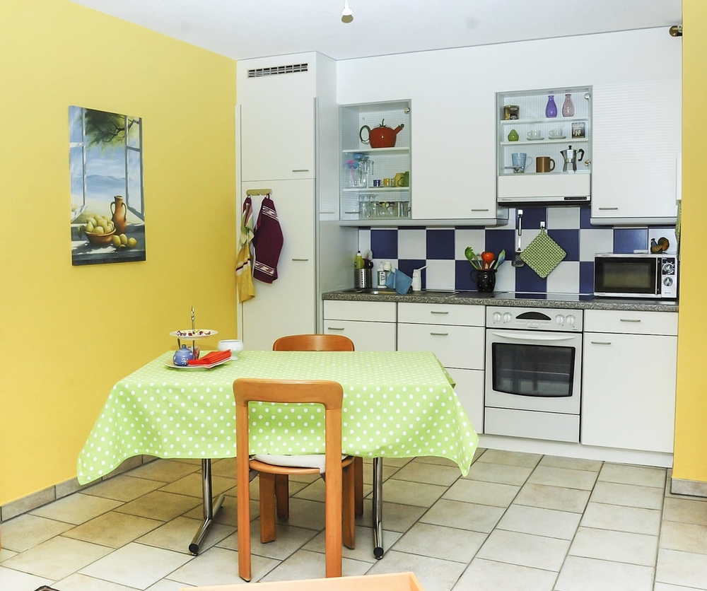 Studio: Ansicht der Einbauküche mit Esstisch im Vordergrund